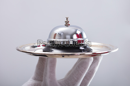 waiter hand holding service bell in