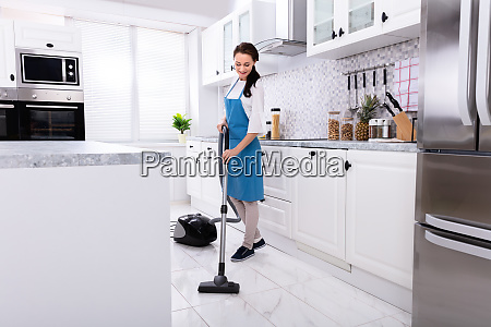 janitor cleaning kitchen floor with vacuum