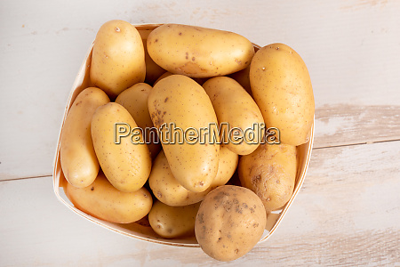 fresh organic potatoes on wooden table