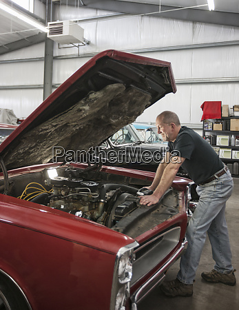 a senior car mechanic working on