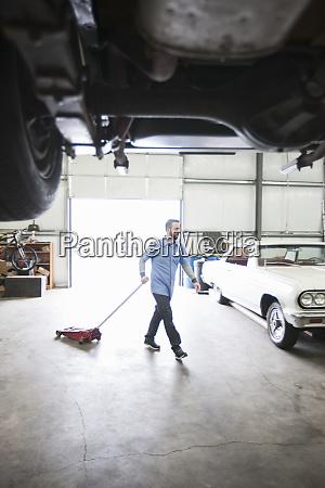 a male car mechanic pulls a