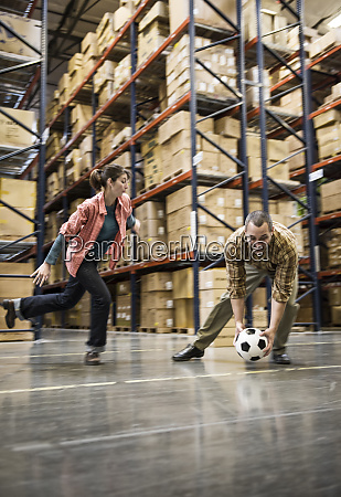 two warehouse workers playing soccer during