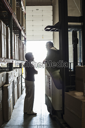two warehouse employees talking over an