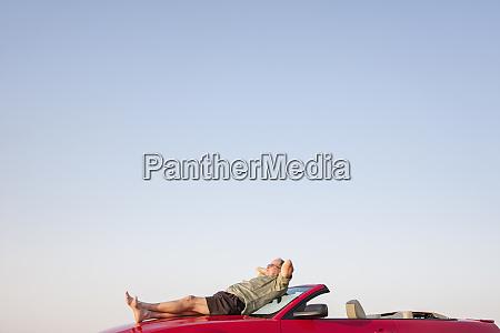 kaukasische maennliche entspannend auf der motorhaube