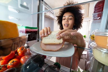 woman taking sandwich from plate in