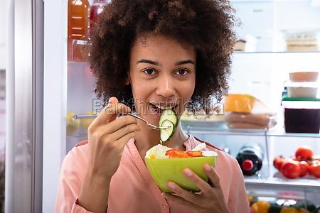 happy woman essing salat in bowl