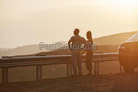 senior couple watching a sunset from
