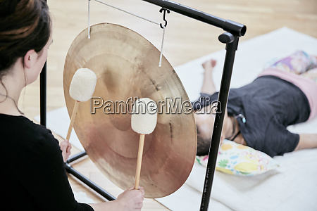 woman striking a large gong with