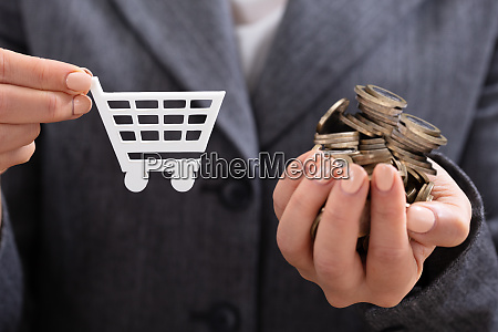 businesswomans hand holding coins and shopping