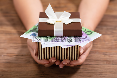 hand holding gift box filled with