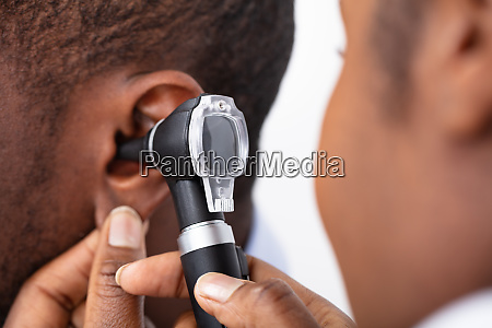 doctor examining male patients ear