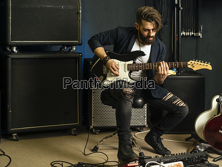 handsome man playing an electric guitar