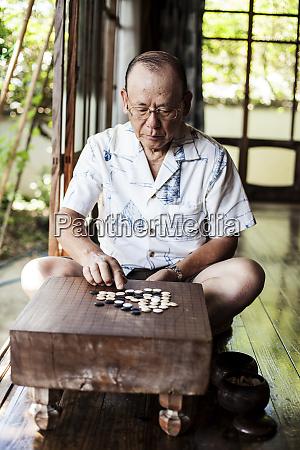 japanese man sitting on floor on