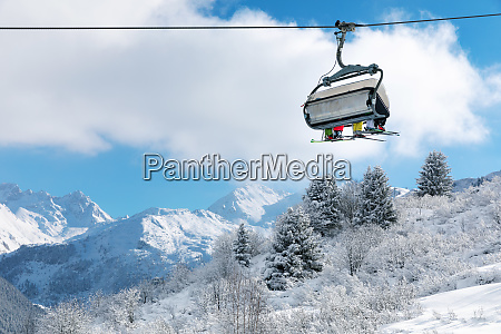 skiers in chairlift above beautiful snowy