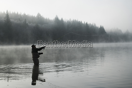 silhouette of fisherman fly fishing for