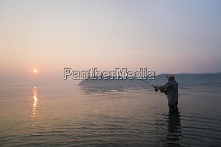 senior caucasian male fly fishing for