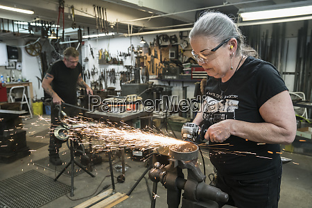 caucasian female blacksmith grinding on a