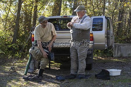 two caucasian male fly fishermen enjoy