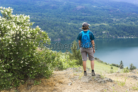 a female hiker stands looking out