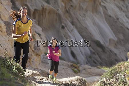 two women running in sandstone area