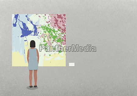 woman looking at abstract painting in