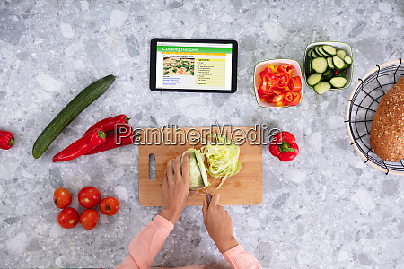womans hand cutting cabbage with digital