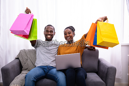 happy couple with laptop holding colorful