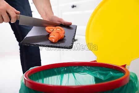 mann wirft tomaten scheibe in papierkorb