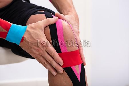man applying kinesiology tape on his