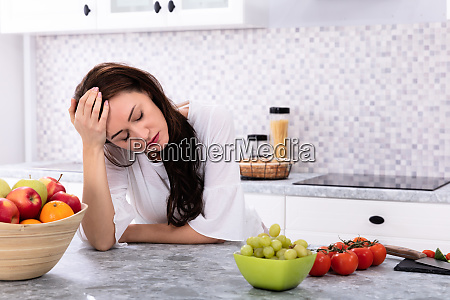 upset woman leaning on kitchen counter