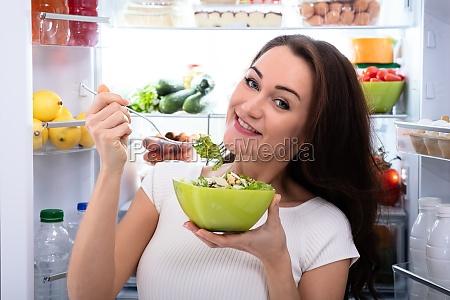 glueckliche frau essen salat in schuessel