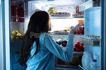 woman standing in front of refrigerator