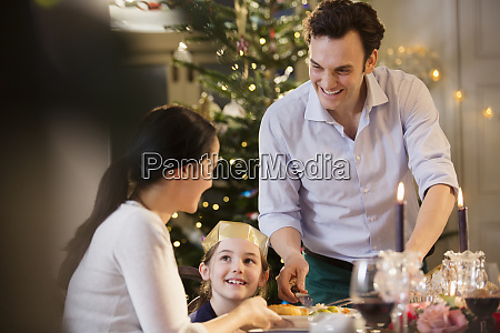 glueckliche familie geniesst candlelight weihnachtsessen
