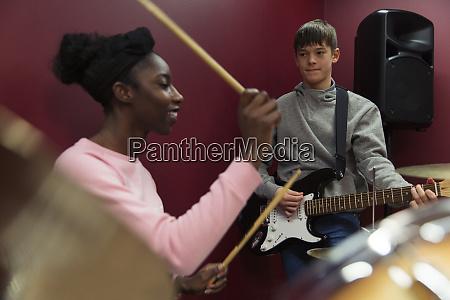 teenage musicians recording music playing guitar