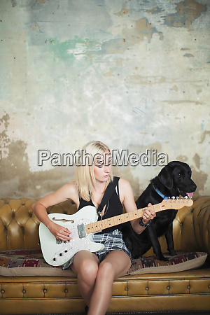 young woman with dog playing electric