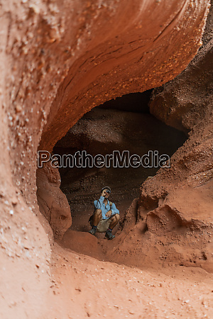 young man sitting in a cave