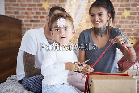 portrait of boy opening christmas present