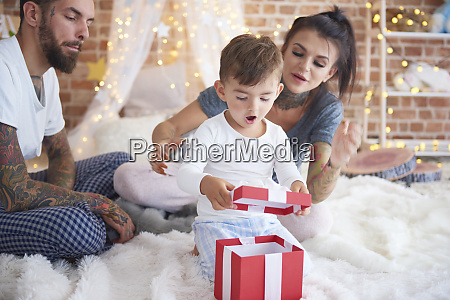 surprised boy opening christmas present with