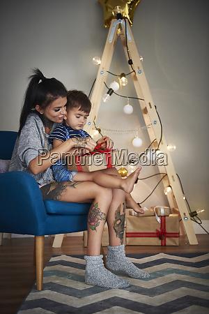 junge eroeffnet weihnachtsgeschenk mit seiner mutter