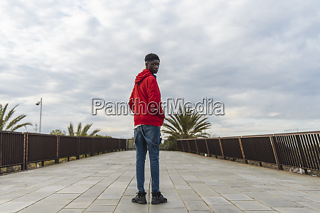 young black man standing outdoors looking