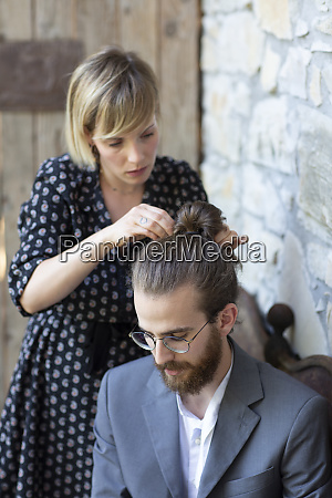 woman doing hair of young man
