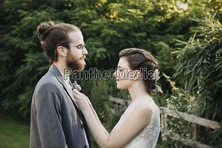 bride adjusting grooms suit outdoors