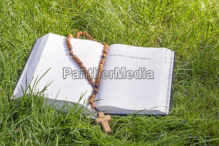 bibel mit rosenkranz auf gruenem gras