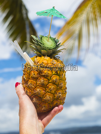womans hand holding fresh pineapple with