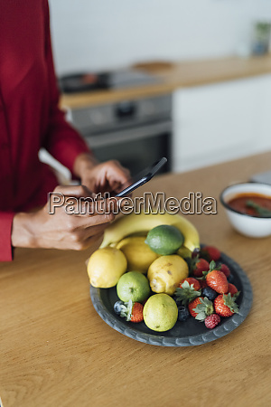 woman taking pictures of fruits on