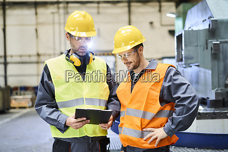 two men wearing protective workwear holding