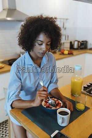 woman having breakfast in her kitchen