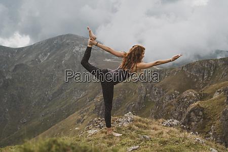 rothaarige frau die yoga auf einem