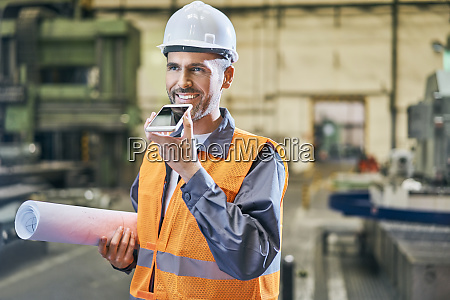 smiling man holding blueprints and using