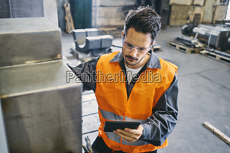 man with tablet wearing protective workwear